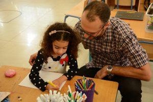 Mädchen mit dunklen Locken malt ein Bild der Vater sieht ihr zu