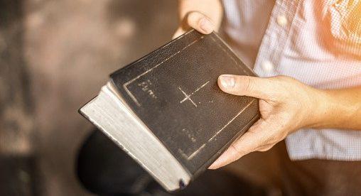 Mann hält Bibel in Händen