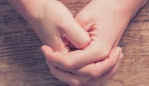 gefaltete Hände auf Holztisch