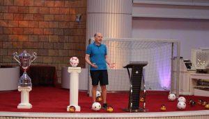 Daniel Müller vom Missonswerk Karslruhe im Fussballtrikot auf Bühne neben ihm große Pokale Das Spiel deines Lebens Misssionswerk Karlsruhe Weltmeisterschaft