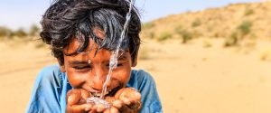 Junge Indien trinkt Wasser aus der Hand