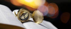 Geöffneter Kompass liegt auf aufgeschlagenem Buch Missionswerk Karlsruhe Bleib auf Kurs