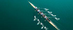 4er Ruderboot von oben symbolisiert Einssein grünes Wasser