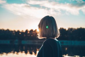 Frau, die bei Sonnenuntergang aufs Wasser schaut Missionswerk Karlsruhe Ermutigung der Woche Wichtiger als alles andere